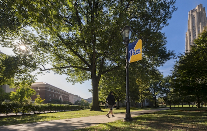 A view of campus including a blue and gold Pitt banner